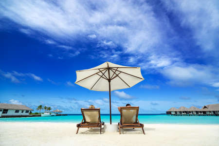 the chaise lounge: Couple on a tropical beach at Maldives