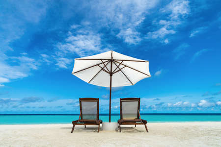 Beach lounger and umbrella on sand beach  Concept for rest, relaxation, holidays, spa, resort