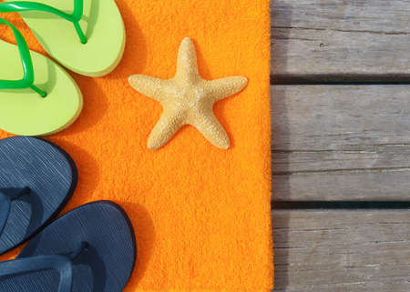 Beach slippers, towel and starfish on wood background  Concept of leisure and travel photo