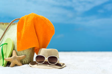 Beach slippers, towel and starfish on wood background  Concept of leisure and travel