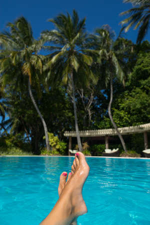 long toes: Close-up of female foot in the blue water on the tropical pool. Vacation holidays.