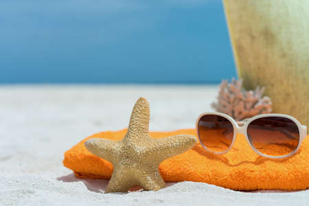 Summer beach bag with towel, sunglasses and coral on sandy beach photo