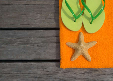 Beach slippers, towel and starfish on wood background. Concept of leisure and travel photo
