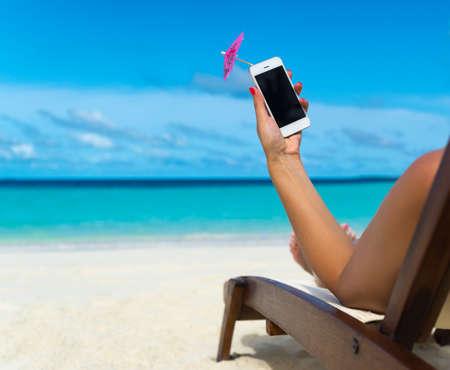 Jong meisje dat op een strand ligstoel met de mobiele telefoon in de hand op het tropische eiland Stockfoto
