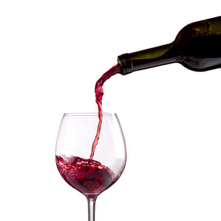 Red wine being poured into wine glass on white background