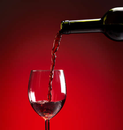 Red wine being poured into wine glass on red background Stock Photo