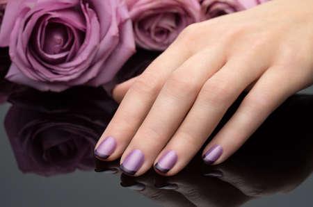 美しいマニキュア、ポーランドは、スミレ色の色です。花の背景。