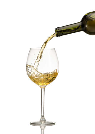 White wine being poured into wine glass on white background