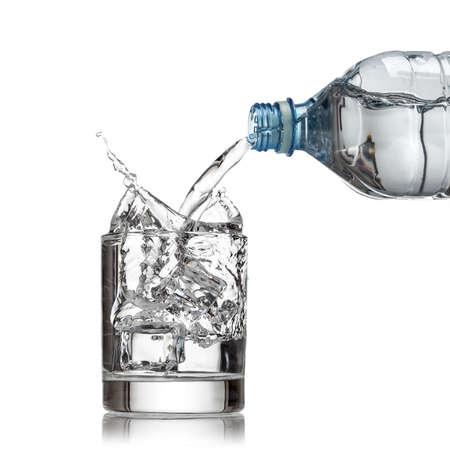 冷たい水のボトルは、白い背景の上のガラスに水を注ぐ