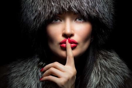 Fur Fashion. Beautiful Girl with red lips and manicure in Fur Hat. Winter Woman Portrait