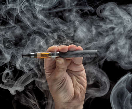 Hand holding an electronic cigarette over a dark background photo