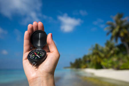 astray: Close up of the hand holding a magnetic compass over a landscape view  travelling in the nature backgrounds Stock Photo
