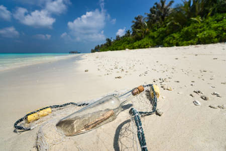 ashore: Message in a bottle washed ashore on a tropical beach.