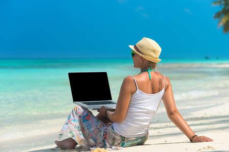 ラップトップ コンピューターとエキゾチックな熱帯のビーチの女性 写真素材