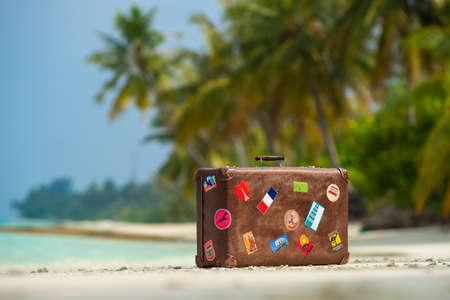 Travel uitstekende koffer is alleen op een strand