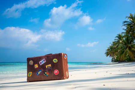 Travel  vintage suitcase is alone on a beach