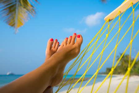 playas tropicales: pies de la mujer en la hamaca en la playa