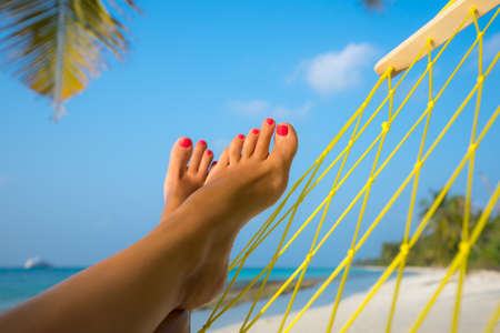 woman feet in hammock on the beach