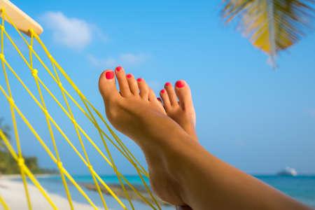 pies bonitos: pies de la mujer en la hamaca en la playa