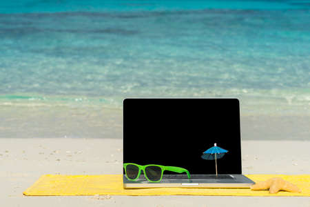 Computer notebook op strand - zakelijke reizen achtergrond