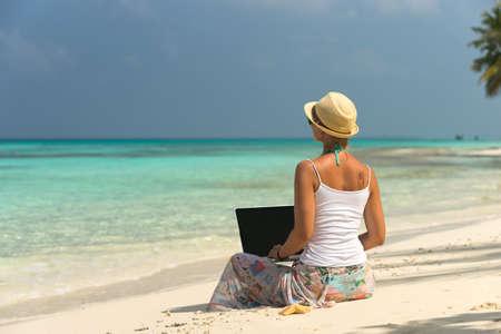 Vrouw op exotische tropisch strand met laptop computer Stockfoto
