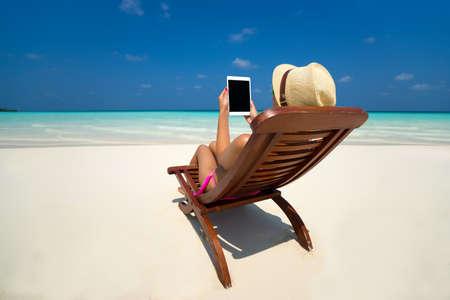 the working day: En blanco tablet PC vacía en manos de las mujeres en la playa Foto de archivo