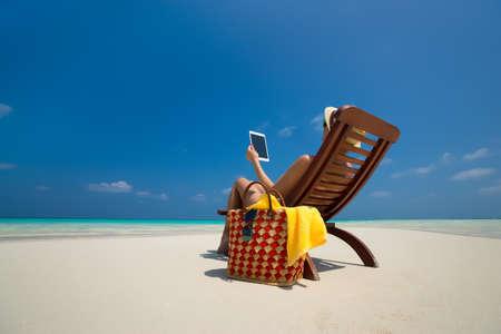 ビーチで女性の手で空白の空のタブレット コンピューター