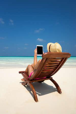 Lege lege tablet-computer in de handen van vrouwen op het strand