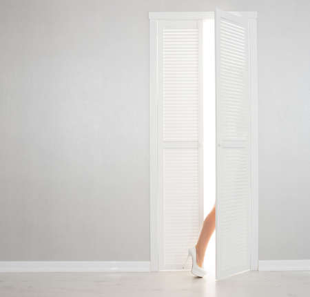 Women leg in white shoe looks out of the open door Stock Photo