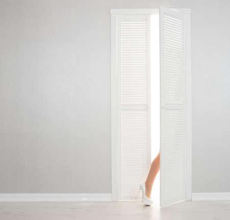 no heels: Women leg in white shoe looks out of the open door Stock Photo