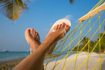 beautiful feet: woman feet in hammock on the beach