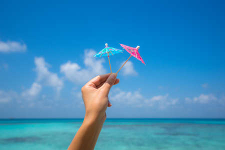 cocktail umbrella: Picture of cocktail umbrella on the tropical beach, vacation. Traveller dreams concept Stock Photo