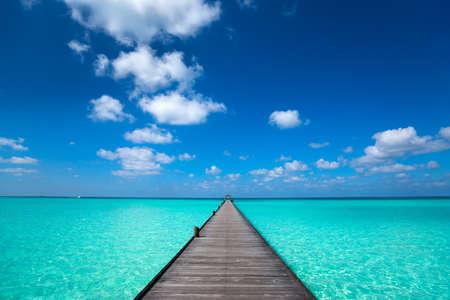 青い海と空の背景を持つ木製の桟橋