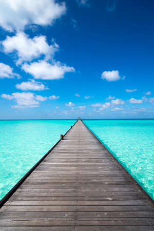 Drewniane molo z błękitnego morza i nieba tle
