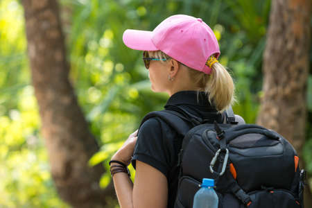 tilt views: Young tourist with backpack walking in tropical jungle