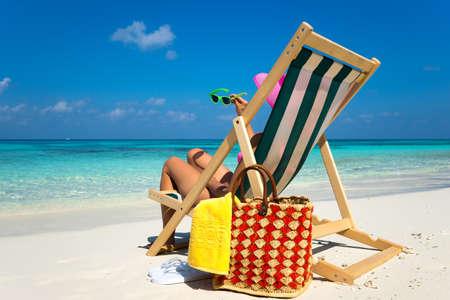 jovenes felices: Chica joven que miente en una tumbona de playa con gafas en la mano en la isla tropical Foto de archivo