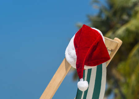 panoramic beach: Sun lounger with Santa hat at beautiful tropical beach with white sand and turquoise water, perfect Christmas vacation Stock Photo