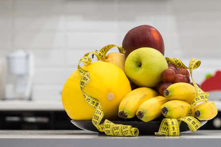 Concept of diet. Low-calorie fruit diet. Diet for weight loss. Plate with measuring tape and fruits on the table. Vegetarian diet for weight loss. Wellness.