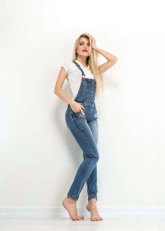 overalls: Portrait of stylish blond young woman,  wearing jeans overalls Stock Photo