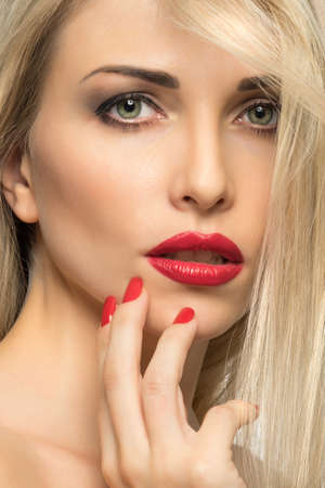seductive women: Close-up portrait of sexy woman lips with red lipstick and red manicure
