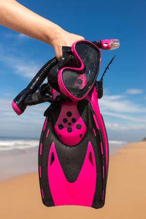 symbol sport: Frau h�lt Maske und Flossen zum Schwimmen auf dem Hintergrund der azurblauen Meer