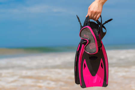 sport background: Woman holding mask and flippers for swimming on the background the azure sea Stock Photo