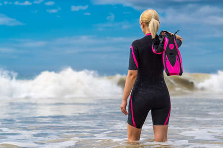 water sport: Woman holding mask and flippers for swimming on the background the azure sea Stock Photo
