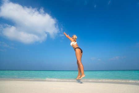 Mujer joven que salta en la playa, nube de captura Foto de archivo