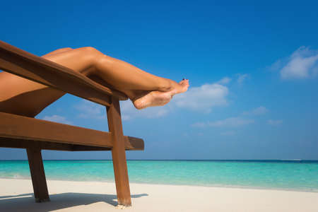 lounger: Young woman sunbathing on lounger. Legs. Stock Photo