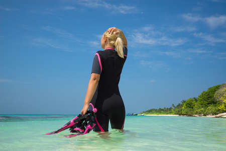 going places: Woman holding mask and flippers for swimming on tropical beach