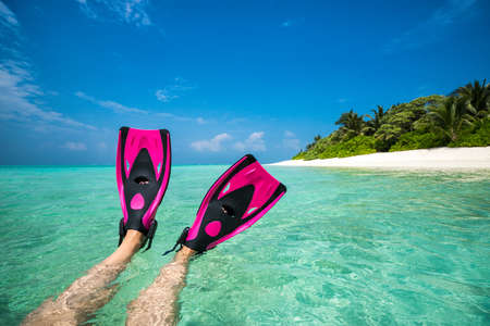 vacation beach: Woman relaxing on summer beach vacation holidays lying in sand. Flippers in legs. Diver fins