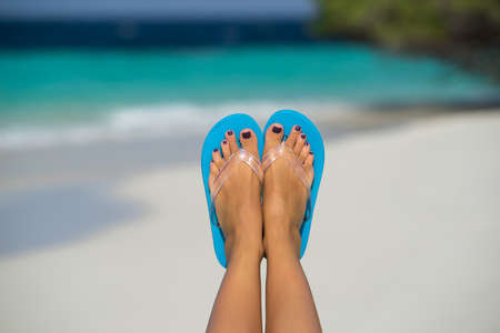 long toes: Close-up of female foot in the blue water on the tropical beach. Vacation holidays.