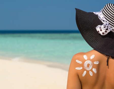 Donna con crema solare a forma di sole