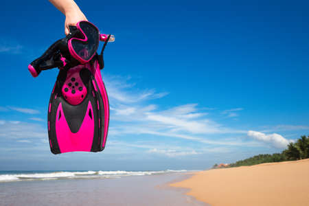 going places: Woman holding mask and flippers for swimming on the background the azure sea Stock Photo